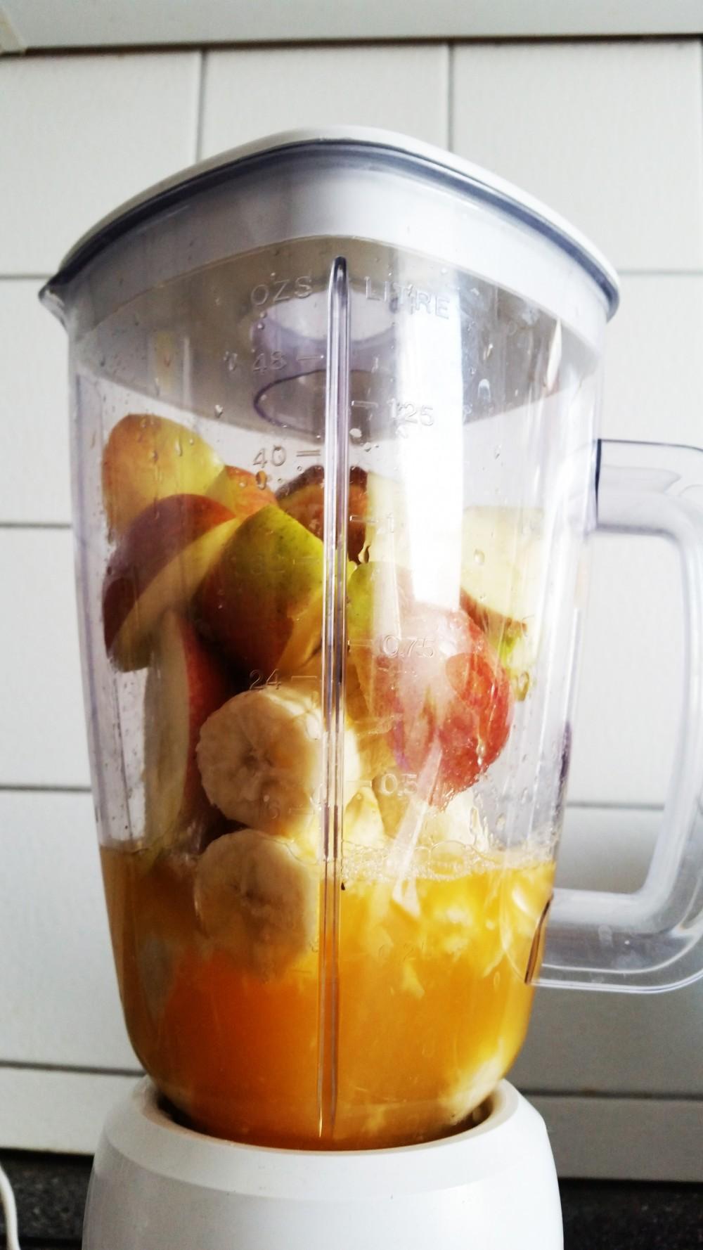 Apfel, Bananen und Orangensaft im Mixer
