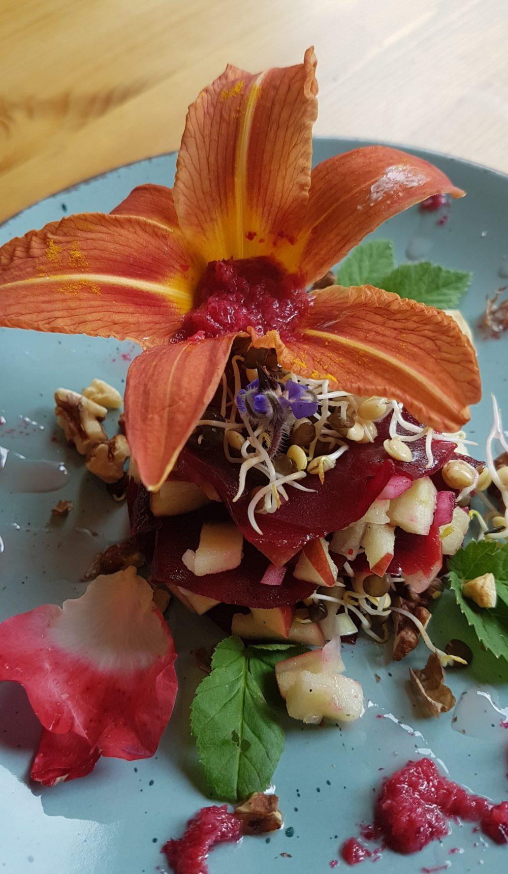 Sommerlicher Salat, dekoriert mit Wildkräuterpesto gefüllten Taglilien