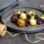 Rotkohlpüree mit Kartoffelklößen, einem Minibratapfel und karamellisierten Cranberries