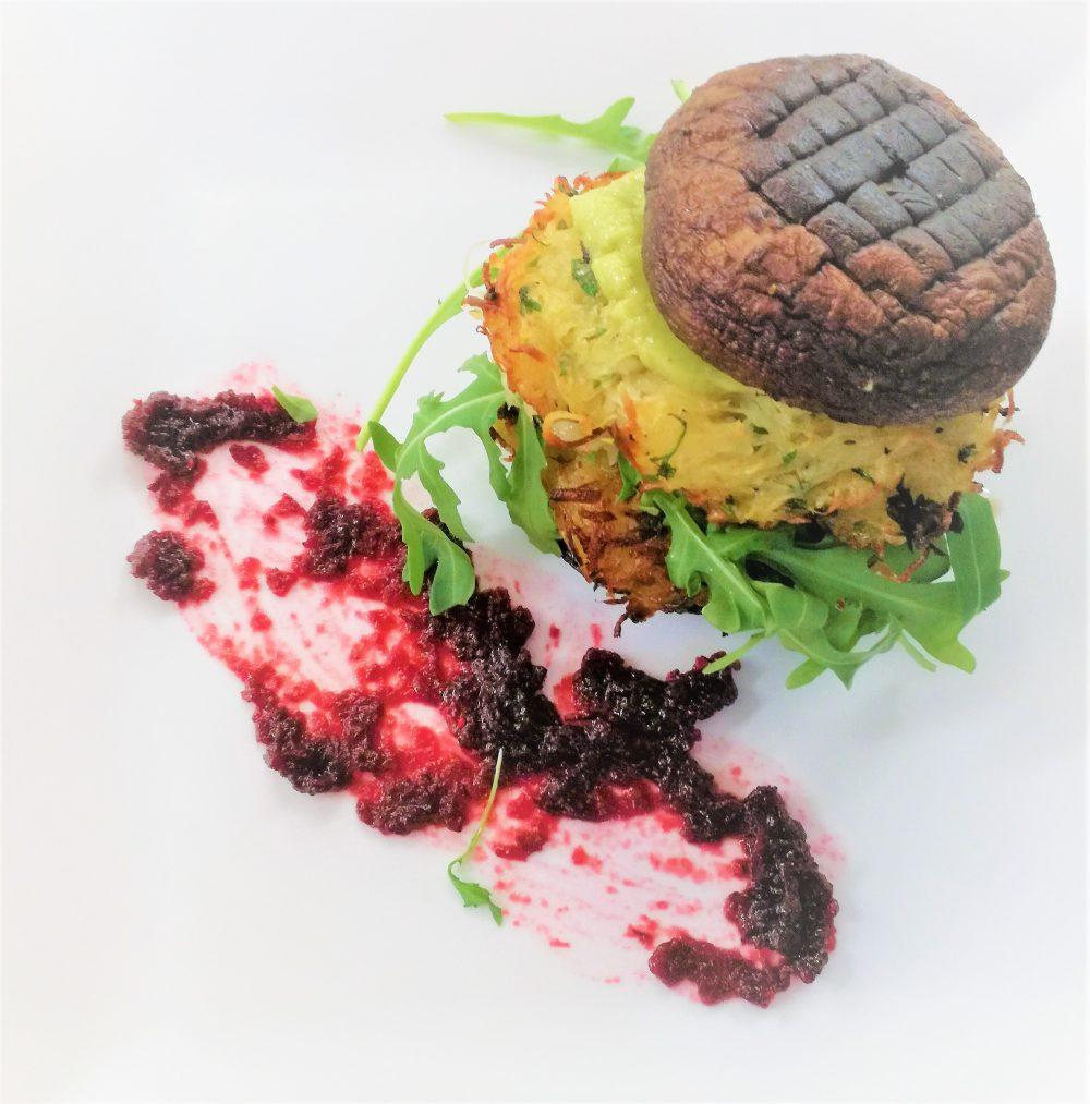 Portobello-Burger mit Kartoffel-Pastinaken-Rösti frischem Rucola und Avocadokrem und Cranberrytunke